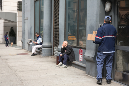 addressee: NEW YORK, USA - Apr 28, 2016: Delivery service worker delivers package to addressee. Two men are resting sitting on the porch. One of them is reading a newspaper. A girl is walking with a dog
