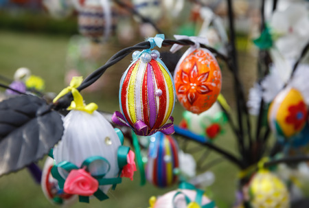UZHGOROD, UKRAINE - Apr 08, 2017: Folk art and festival of Easter Eggs. Easter holiday. Multicolored Easter eggs hanging on artificial trees