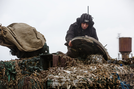 LUGANSK REG, UKRAINE - Apr 12, 2017: Armored units on combat duty. The tank man prepares the tank for training firing. Weaponry and military equipment of the armed forces of Ukraine