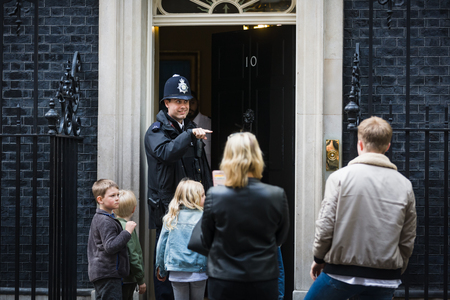 ministers: LONDON, UK - Apr 19, 2017: Metropolitan police officer on duty at 10 Downing Street communicates with a group of people on the doorstep of the prime ministers residence in the UK Editorial