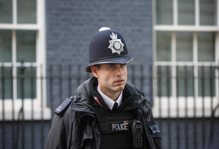LONDON, UK - Apr 19, 2017: Metropolitan police officer on duty at 10 Downing Street official residence of First Lord of the Treasury, headquarters of Her Majestys Government, office of Prime Minister Editorial
