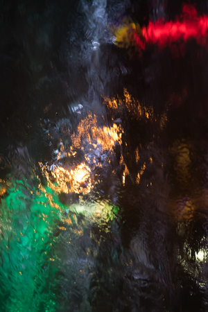 Abstract water grops background. Water drops and splashing on glass on a dark background illuminated with colored lights. Stream and drops flowing down the glass Stock Photo