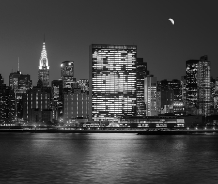 Manhattan at Night. New York City skyline with lights and reflections. Black and white image