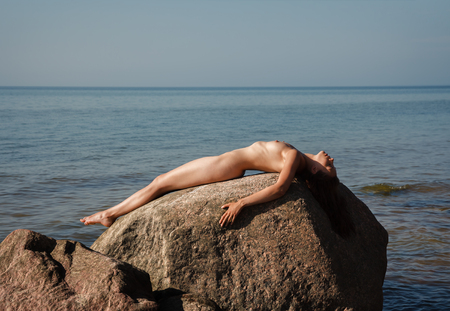 Naked girl outdoors enjoying nature. Beautiful young nude woman lies on large stones against the sea and sunbathing. Lady with nude perfect body on the nudist beach