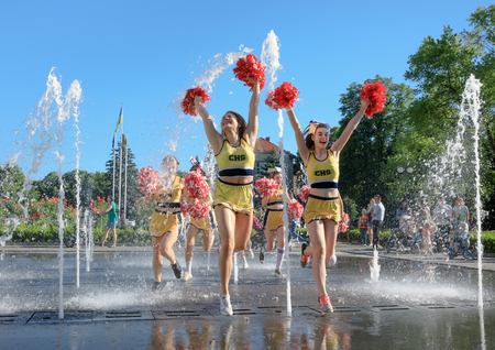 UZHGOROD, UKRAINE - May 28, 2017: Cheerleaders Team. Group of happy Cheerleaders enjoy jogging through the fountain after the performance on the student holiday