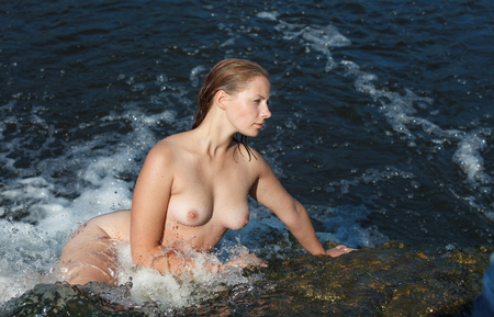 A young beautiful naked woman enjoys the coolness of lying down in streams of water in a waterfall Stock Photo