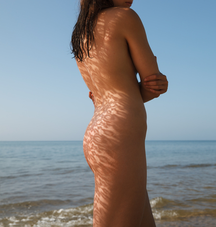 Nude woman with lace shadow on the body in the sun light Фото со стока