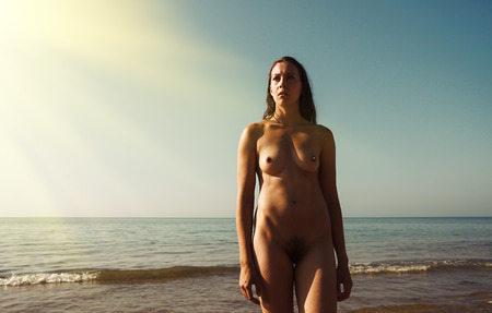 Naked girl outdoors enjoying nature. Beautiful young nude woman against the sea. Lady with nude perfect body on the nudist beach. Summer paradise