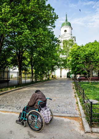KIEV, UKRAINE - May 02, 2017: A homeless disabled man in a wheelchair sleeps early in the morning near the church