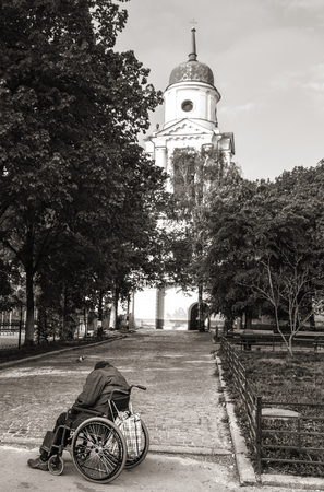 KIEV, UKRAINE - May 02, 2017: Black and white image of an homeless disabled man in a wheelchair sleeps early in the morning near the church
