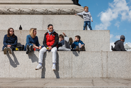LONDON, UK - Apr 19, 2017: Adults and children rest at the base of the Nelson column. Nelson Column is a monument in Trafalgar Square in central London built to commemorate Admiral Horatio Nelson
