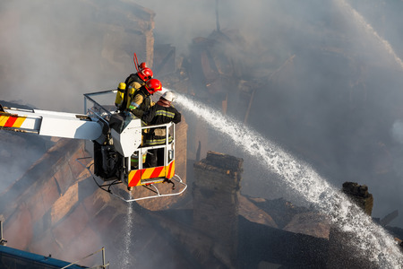 KIEV, UKRAINE - Jun 20, 2017: Ukrainian firefighters try to extinguish a fire in a three-story house on Khreshatyk street, the main street in Kiev. Firefighters in action