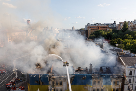 KIEV, UKRAINE - Jun 20, 2017: Ukrainian firefighters try to extinguish a fire in a three-story house on Khreshatyk street, the main street in Kiev. Firefighters in action