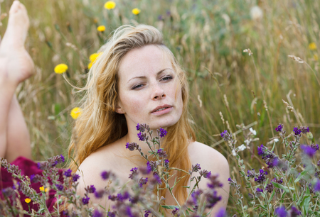 Artistic portrait of freckled woman on natural background. Young woman enjoying nature among the flowers and grass. Close up summer portrait