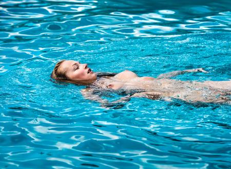 Jeune femme nue aime nager dans la piscine Banque d'images - 82664923