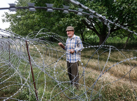 facto: KHURVALETI, GEORGIA, Jul 19, 2017: Old man on local stand near barbed wire on the separation line with occupied Tskhinvali region Georgias de-facto border with its breakaway region of South Ossetia