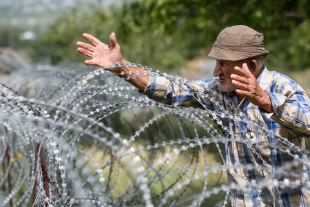 KHURVALETI, GEORGIA, Jul 19, 2017: Old man on local stand near barbed wire on the separation line with occupied Tskhinvali region Georgias de-facto border with its breakaway region of South Ossetia