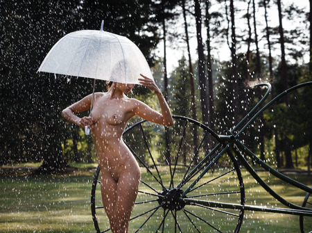 Nude woman outdoors enjoy nature. Young beautiful naked woman with an umbrella on nature under a summer rain and in the rays of sunlight