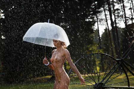 Naakte vrouw buiten genieten van de natuur. Jonge mooie naakte vrouw met een paraplu op aard onder een de zomerregen en in de stralen van zonlicht Stockfoto