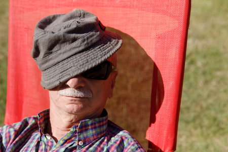 Senior gentleman sitting on bench and relaxing. An elderly man in sunglasses enjoys relaxing on the sun while sitting on a red beach chair and covering his head with a cap. Lifestyle concept photo