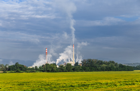 Industrial smoke from chimney on Cloudy sky. Factory pipes. Pipe with smoke. Pipe emissions into the atmosphere. Harmful emissions into the atmosphere.
