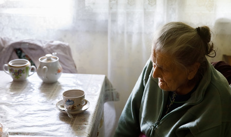 Old depressed woman. An elderly lonely woman sits at a table in the kitchen near the window and drinking tea. Stock Photo