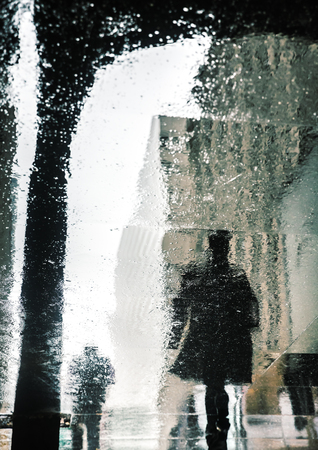 Rain in New York City. Reflections from wet tile slabs. Pedestrians hurry on their business. Reklamní fotografie - 85314299
