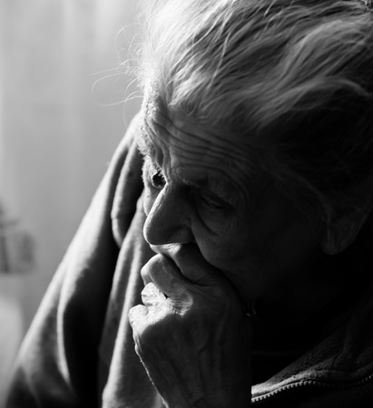 Portrait of a very old tired woman sitting near a window Stock Photo