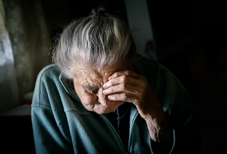 invalidity: Portrait of a very old tired woman sitting near a window Stock Photo
