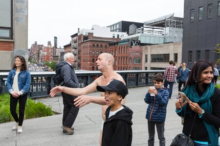 NEW YORK, USA - Apr 29, 2016: A group of Americans and tourists are photographed near the sculpture of a sleepwalker in New York City.  A semi-naked sculpture of a sleepwalking man by Tony Matelli