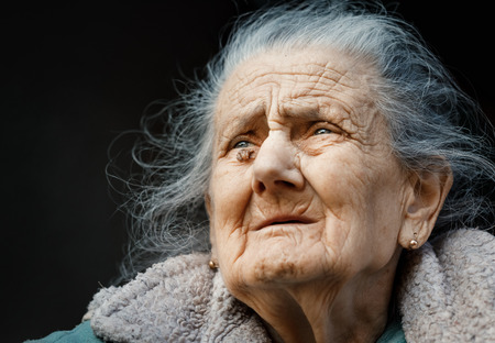 Portrait of a very old and tired of life wrinkled woman outdoors near the wall of her house