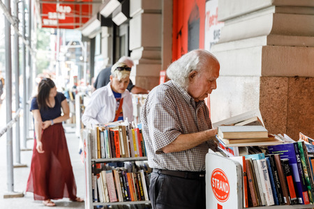 NEW YORK, USA - Sep 16, 2017: Strand Book Store in Manhattan. A gray-haired old man chooses a book to buy