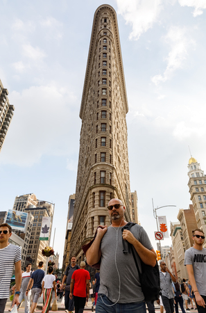 fifth avenue: NEW YORK, USA - Sep 16, 2017: Flatiron Building in NYC. Originally the Fuller Building located at 175 Fifth Avenue in the borough of Manhattan. Middle-aged man listens to music in headphones