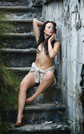 half naked: Emotional half-naked young woman sits on a staircase in an old abandoned concrete building and holds a finger in the mouth. Image in a cold dramatic tone Stock Photo