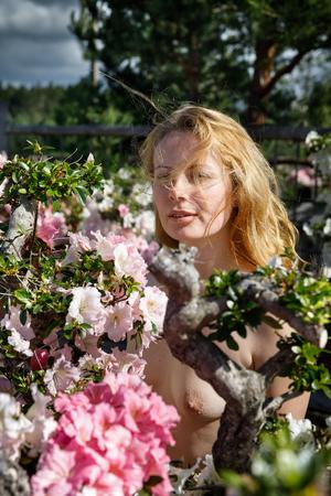 Portret van een naakt blond meisje onder de bloemen van azalea in de stralen van zonlicht