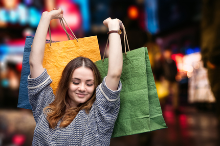 Shopping in New York City. Beautiful young woman with shopping bags during sales season in the big city Stock Photo