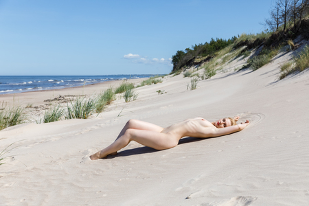 Beautiful girl enjoying nature. Young naked blonde woman enjoying the sea breeze and sunbathing on a sandy beach. Nude woman posing on sea beach