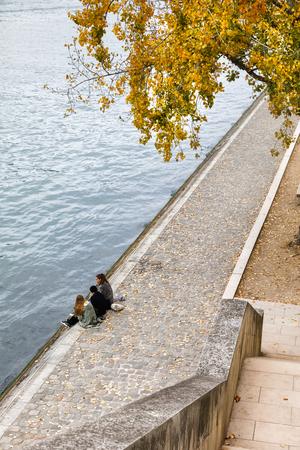 PARIS, FRANCE - Nov 09, 2017: Parisians and tourists walk and rest on the Seine embankment in Paris