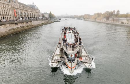 PARIS, FRANCE - Nov 09, 2017: Cruise ship on the Seine in Paris on a cloudy foggy day Редакционное