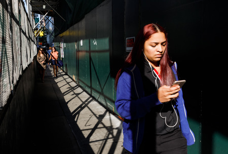 NEW YORK, USA - Sep 17, 2017: Manhattan street scene. Young woman with mobile phone walking on sidewalk with a protective fence near construction works
