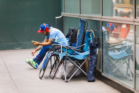 NEW YORK, USA - Sep 16, 2017: Manhattan street scene. Black man sits on folding chairs and listens to music on headphones Editorial