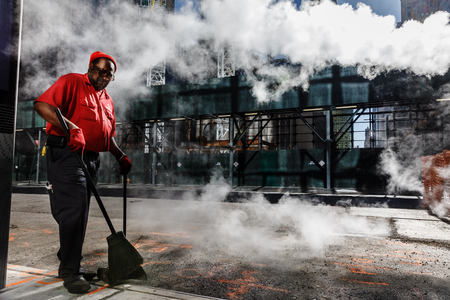 NEW YORK, USA - Sep 23, 2017: Manhattan street scene. Cleaner sweeps the street. Cloud of vapor from the subway on the streets of Manhattan in NYC. Typical view of Manhattan