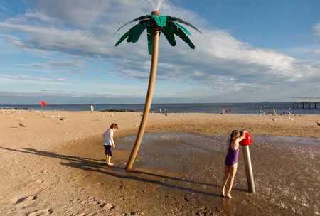 NEW YORK, USA - Sep 23, 2017: Coney Island Beach in NYC. Children play with a fountain in the form of a palm tree. Coney Island is well known as the site of amusement parks and a seaside resort