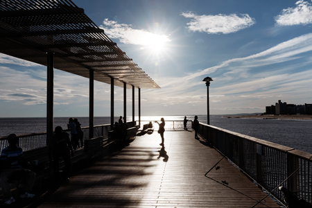 NEW YORK, USA - Sep 23, 2017: Silhouettes of peoples on Steeplechase Pier on Coney Island Beach in New York City. Coney Island is well known as the site of amusement parks and a seaside resort Editorial