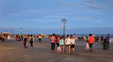 NEW YORK, USA - Sep 23, 2017: Coney Island Beach in NYC. Vacationers walking on the shore in evening time. Coney Island is well known as the site of amusement parks and a seaside resort