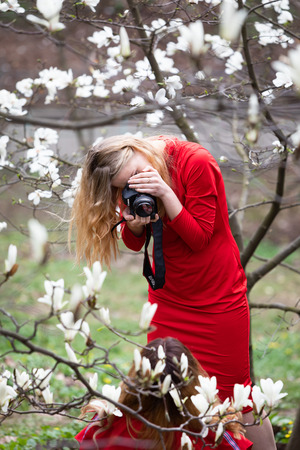 KYIV, UKRAINE - Apr 17, 2018: People enjoy magnolia blossoms. People photograph and making selfies in blossoming magnolia garden. Blossoming magnolia trees attract thousands of visitors every spring