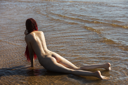 Beautiful girl outdoors enjoying nature. Young naked woman with scarlet dreadlocks enjoys the sea on the coast 版權商用圖片
