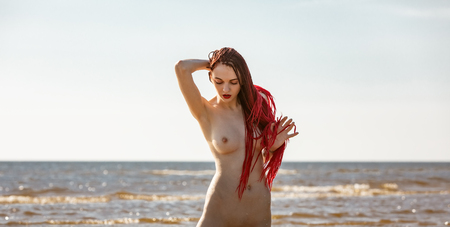Beautiful girl outdoors enjoying nature. Young naked woman with scarlet dreadlocks enjoys the sea on the coast Archivio Fotografico