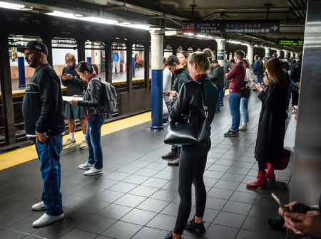 New York, USA - Sep 24, 2018: New York and New Yorkers. New York City Subway. Passenger with smartphones waiting for their train