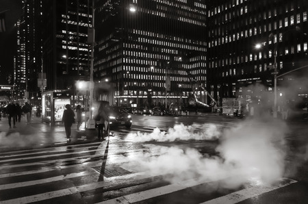 New York, USA - Sep 24, 2018: Manhattan street scene. Cloud of vapor from the subway on the streets of Manhattan in NYC at night. Typical view of Manhattan
